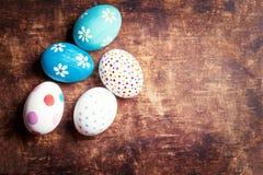 Composición de Pascua con los huevos coloridos en fondo de madera con Foto de archivo libre de regalías