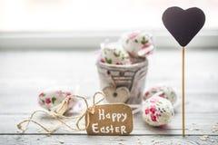 Composición de Pascua con los huevos en un cubo Fotos de archivo