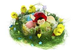 Composición de Pascua con los huevos pintados, los pollos divertidos y la mariquita Foto de archivo libre de regalías