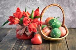 Composición de Pascua con los tulipanes rojos, el corazón de madera y una cesta de Imagen de archivo