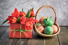 Composición de Pascua con los tulipanes rojos, la caja de regalo y una cesta de cuesta Imágenes de archivo libres de regalías