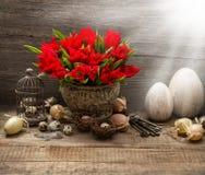 Composición de pascua del vintage con los huevos, tulipanes rojos Foto de archivo libre de regalías