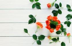 Composición de rosas frescas en un fondo de madera blanco imagen de archivo