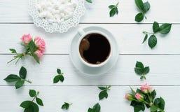 Composición de rosas frescas, taza del café, varshmallows en un fondo de madera blanco Wiew superior imagenes de archivo