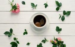 Composición de rosas frescas, taza del café, varshmallows en un fondo de madera blanco Wiew superior foto de archivo libre de regalías