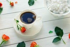 Composición de rosas frescas, taza del café, varshmallows en un fondo de madera blanco Wiew superior fotos de archivo