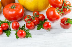 Composición de tomates grandes, cereza, calabaza, jugo en un padrenuestro Foto de archivo