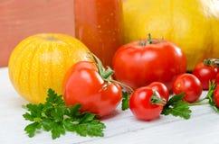 Composición de tomates grandes, cereza, calabaza, jugo en un padrenuestro Fotos de archivo