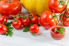 Composición de tomates grandes, cereza, calabaza, jugo en un padrenuestro Imagen de archivo