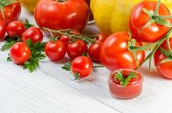 Composición de tomates grandes, cereza, calabaza, jugo en un padrenuestro Fotografía de archivo