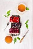 Composición de tortas con diversa fruta y una taza de té Foto de archivo libre de regalías