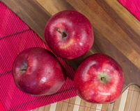 Composición de tres manzanas rojas en un tablero de madera imagen de archivo