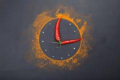 Composición de un reloj de las especias y de las pimientas de chile en un fondo negro Imagen de archivo