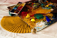 Composición de una paleta artística, de una fan de la mano, de acuarelas, de acrílicos, de una espátula, de una bola transparente Foto de archivo