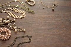 Composición decorativa de la joyería del ` s de las mujeres en fondo oscuro de madera Fotografía de archivo