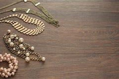 Composición decorativa de la joyería del ` s de las mujeres en fondo oscuro de madera Fotos de archivo libres de regalías