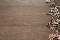 Composición decorativa de la joyería del ` s de las mujeres en fondo oscuro de madera Imágenes de archivo libres de regalías