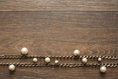 Composición decorativa de la joyería del ` s de las mujeres en fondo oscuro de madera Imagen de archivo