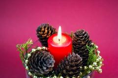 Composición decorativa de la Navidad de la vela roja, conos del pino Fotos de archivo libres de regalías