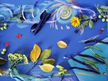 Composición decorativa del otoño de las flores amarillas, hojas, habas de espárrago, frutas, documento coloreado sobre el papel a Imagen de archivo