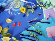 Composición decorativa del otoño de las flores amarillas, hojas, habas de espárrago, frutas, documento coloreado sobre el papel a Foto de archivo