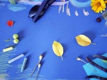 Composición decorativa del otoño de las flores amarillas, hojas, habas de espárrago, frutas, documento coloreado sobre el papel a Imagen de archivo libre de regalías