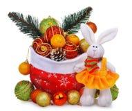 Composición del Año Nuevo con el bolso de Papá Noel, las chucherías de la Navidad y el conejo blanco de la muñeca en vestido amar Imágenes de archivo libres de regalías