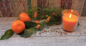 Composición del Año Nuevo con las mandarinas, la rama del arborvitae, las velas y los árboles de navidad Foto de archivo libre de regalías