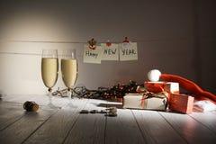 Composición del Año Nuevo de dos vidrios de champán, de regalos envueltos y de guirnaldas poniendo en la tabla El Año Nuevo de la Imágenes de archivo libres de regalías