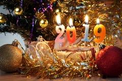 Composición 2019 del Año Nuevo Decoraciones del día de fiesta y velas ardientes Foto de archivo libre de regalías