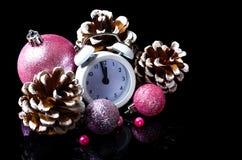 Composición del Año Nuevo: reloj, conos y bolas de la Navidad aisladas Imagen de archivo