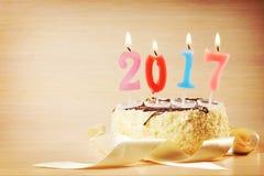 Composición 2017 del Año Nuevo Torta y velas ardientes Foto de archivo