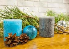 Composición del Año Nuevo y de la Navidad con los conos de abeto y dos velas Imagen de archivo libre de regalías