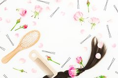Composición del blog de la belleza con el peine para diseñar del pelo, el pasador y las flores rosadas en el fondo blanco Endecha Imagen de archivo