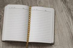Composición del capítulo Cuaderno y decoraciones de oro en fondo de madera Visión superior Foto de archivo libre de regalías
