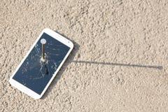 Composición del clavo y del smartphone del metal Foto de archivo