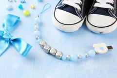 Composición del clip del pacificador para el bebé, zapatos y nudo del arco Foto de archivo libre de regalías