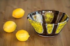 Composición del cuenco de cerámica brillante y de limones amarillos Fotografía de archivo