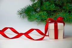 Composición del día de fiesta de la Navidad Regalo del Año Nuevo en la caja blanca con la cinta roja en fondo ligero con el árbol Imágenes de archivo libres de regalías