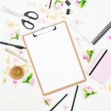 Composición del espacio de trabajo de la educación con el tablero, el cuaderno, las flores y los accesorios en el fondo blanco En Fotos de archivo libres de regalías