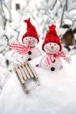 Composición del invierno con el muñeco de nieve y el trineo Foto de archivo libre de regalías