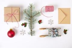 Composición del marco de la Navidad Regalo de la Navidad, rama del pino, bolas rojas, sobre, copos de nieve de madera blancos, ci Foto de archivo libre de regalías