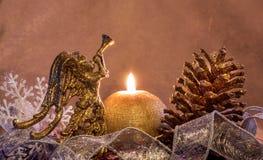 composición del Nuevo-año con una vela por un cono y un ángel del oro Feliz Navidad y Feliz Año Nuevo Foto de archivo libre de regalías