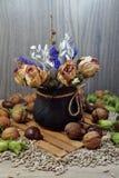 Composición del otoño con las flores y nueces secadas, avellanas y castañas Fotografía de archivo