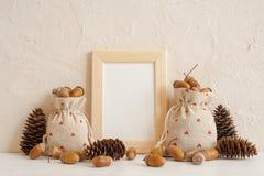 Composición del otoño con mofa encima del marco, de las bellotas en los bolsos de lino y de los conos del pino Otoño, concepto de fotos de archivo libres de regalías