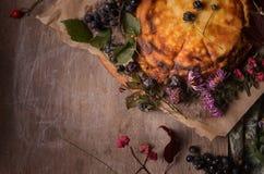 Composición del otoño de las flores, de las bayas y de la torta amarilla fotos de archivo