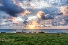 Composición del paisaje del ocaso Cielo, mar, e hierba verde fotografía de archivo