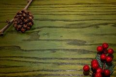 Composición del pinecone de la Navidad, ramas de Hollies en fondo de madera verde fotos de archivo libres de regalías