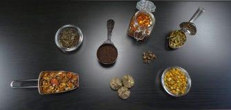 Composición del té con té real y flores del té, jazmín, manzanilla, té negro, té de la salud en el fondo de madera negro imagen de archivo