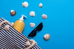 Composición del verano Bolso pelado de la playa con la crema del bronceado, concha marina, gafas de sol Concepto de las vacacione foto de archivo libre de regalías